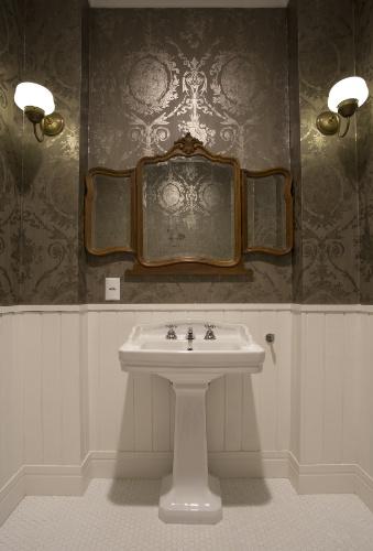 O papel de parede usado para revestir o lavabo social é da Ralph Lauren (Designer Wallcoverings). A moldura inferior que decora a parede é de madeira, em estilo clássico, e acompanha o estilo da louça Celite da Linha Clássica (lavatório com coluna) e as réplicas de luminárias, usadas como arandelas, compradas na Feira do Bixiga. Para finalizar, o piso é de pastilhas sextavadas hexagonais (Atlas), que remetem ao design dos anos 1950, do sobrado reformado pelo escritório SET Arquitetura