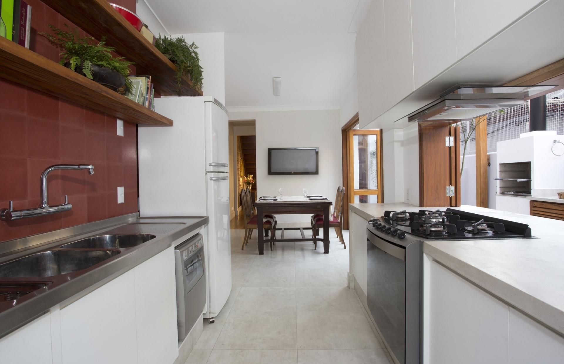 A cozinha tem armários com tampo modulado Mekal e ladrilho hidráulico vermelho revestindo parede da área de trabalhos (à esq.), além de bancada em cimento queimado (Vianarte). A casa fica no bairro da Liberdade, centro de São Paulo, e teve projeto de
