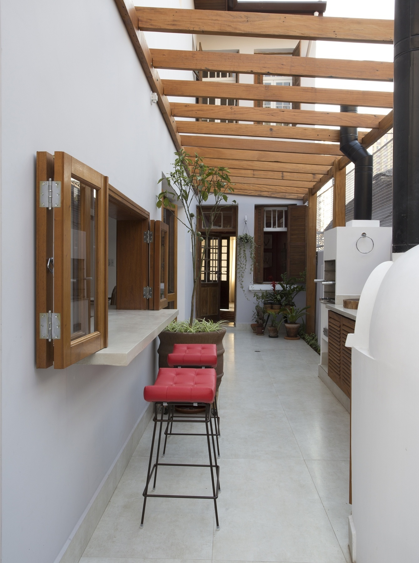 A cozinha é integrada ao espaço gourmet por portas articuladas (camarão) com folhas que deslizam sobre trilhos inseridos no piso de porcelanato (áreas interna e externa). O novo ambiente ocupa a antiga lavanderia (corredor lateral) e funciona como área de lazer e recepção da casa, com churrasqueira e forno de pizza, além de um pergolado em madeira de demolição. O projeto de reforma é do escritório SET Arquitetura para a recuperação da casa na Liberdade, em São Paulo, construída nos anos 1950