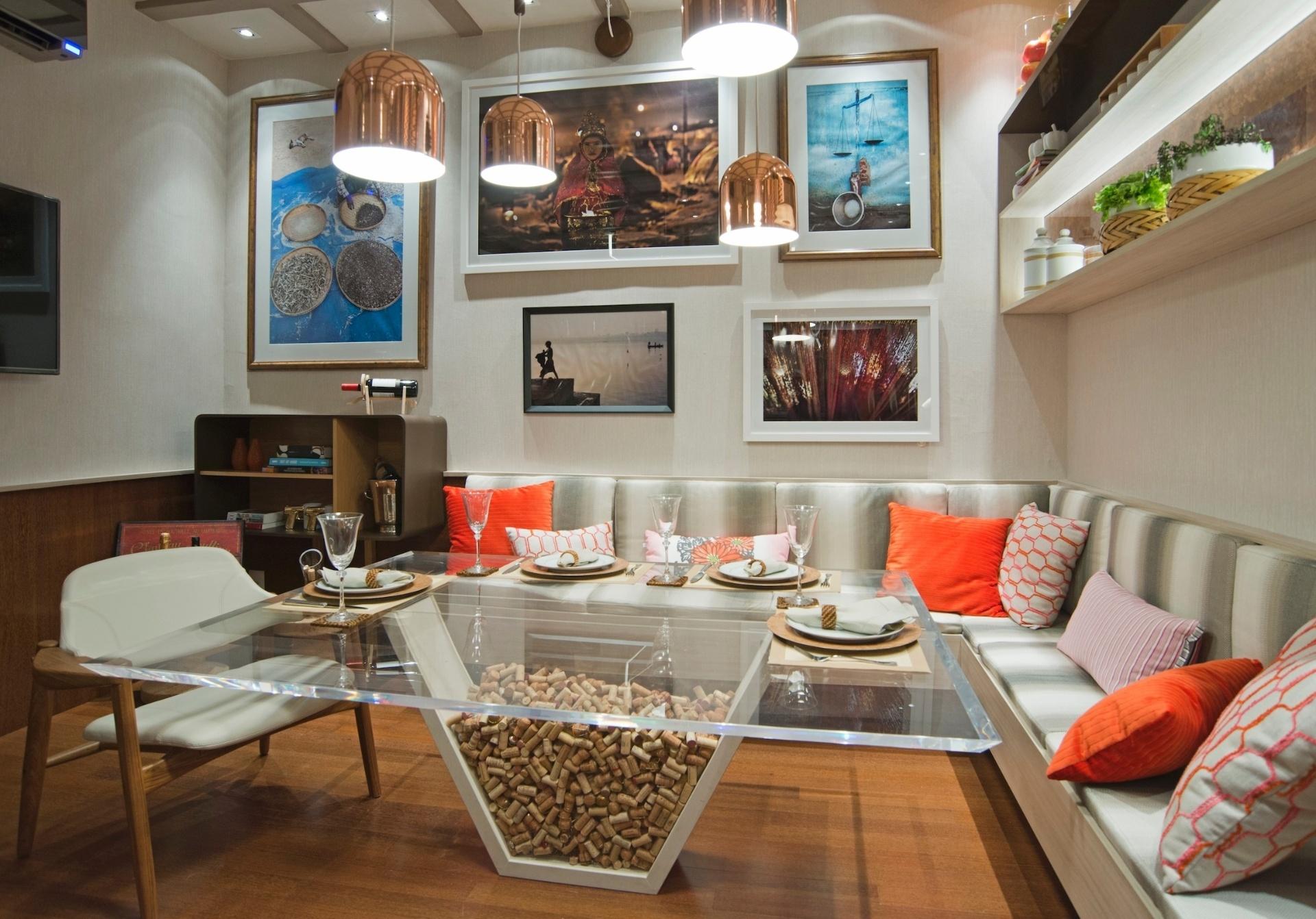 A Sala de Almoço é integrada à Cozinha (foto 11) e ambos os ambientes são projetos assinados por Naiana Lima e Priscilla Ximenes. Nesse espaço social, o sofá em L é combinado à mesa com estrutura de acrílico que