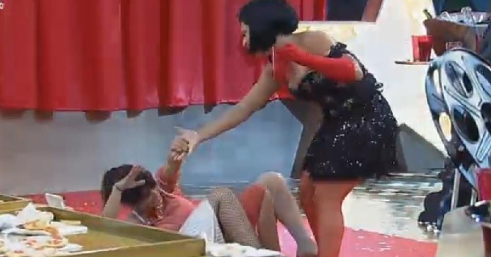 22.nov.2014 - Heloisa Faissol cai no chão e recebe ajuda de Babi Rossi para se levantar na festa Cinema Mudo de