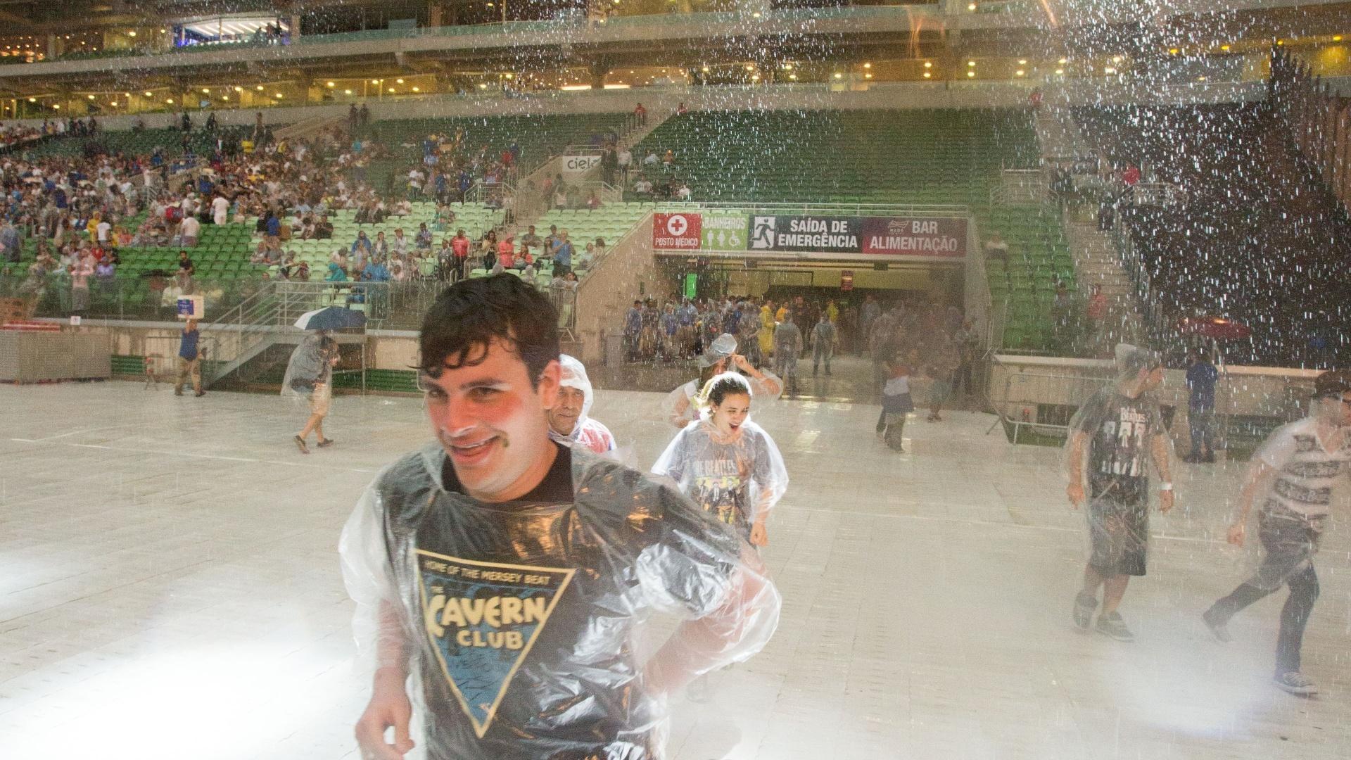 25.nov.2014 - Sob forte chuva, fã de Paul McCartney entra no Allianz Parque, na zona oeste de São Paulo, onde o cantor se apresenta com a turnê
