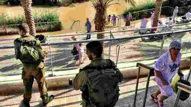 Fiéis cruzam com soldados israelenses ao sair do rio Jordão, na área de Qasr al-Yahud - Marcel Vincenti/UOL