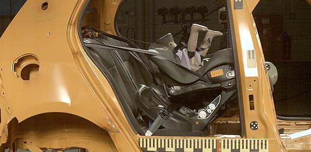 Presilha da cadeirinha Baby Style 333 quebra durante teste, e boneco quase dá cambalhota; numa situação real, bebê bateria a cabeça no banco dianteiro - Reprodução