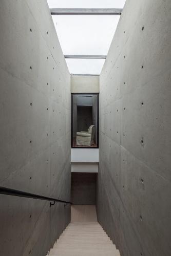 Entre duas paredes de concreto aparente, a escada de ligação do térreo com o pavimento superior recebeu iluminação zenital através da claraboia com fechamento em vidro. Desse ângulo é possível visualizar a sala íntima do primeiro andar. A NSN House tem projeto assinado pelo escritório Biselli Katchborian Arquitetos