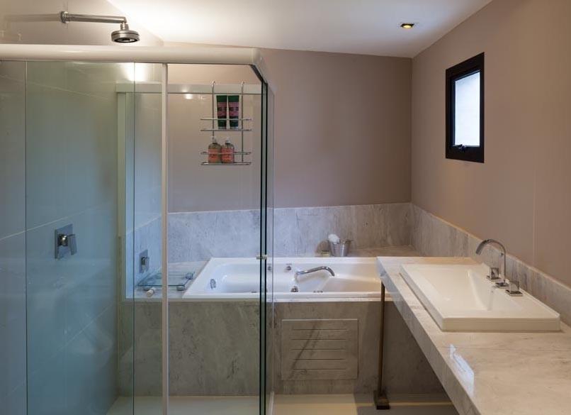 O revestimento em mármore assegura a atmosfera de requinte e elegância ao banheiro da suíte do casal que tem espaço para hidromassagem. A NSN House foi criada pelo escritório Biselli Katchborian Arquitetos