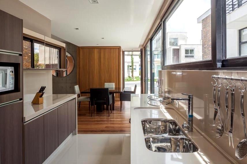 A cozinha e a copa receberam portas corrediças e janelas amplas com fechamento em vidro. O recurso assegura a entrada de intensa luminosidade natural nesses espaços da NSN House, projetada pelo escritório Biselli Katchborian Arquitetos