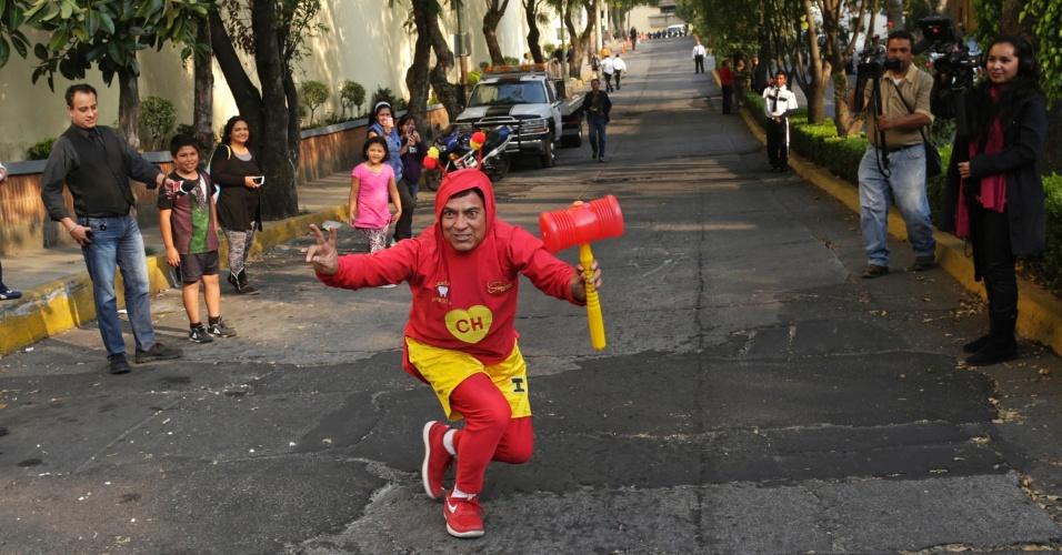 29.nov.2014 - Fã do Chapolin Colorado aguarda a passagem do carro com o corpo de Roberto Bolanõs rumo à Televisa, na Cidade do México