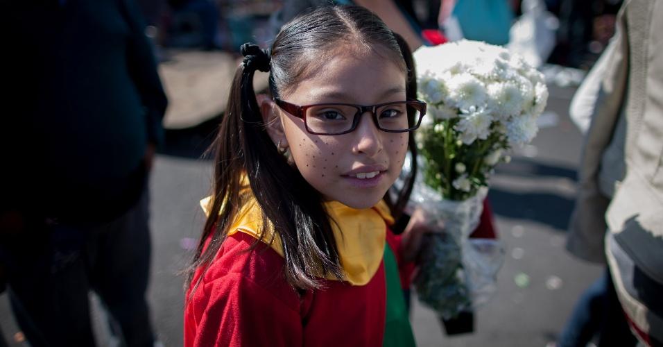 30.nov.2014 - Fantasiada de Chiquinha, fã leva flores a cerimônia de despedida de Roberto Bolaños no Estádio Azteca, na Cidade do México