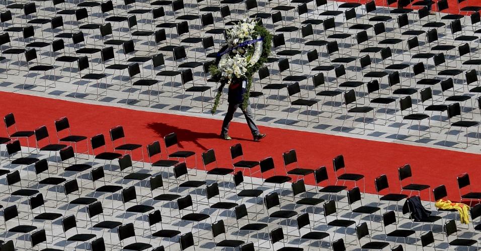 30.nov.2014 - Homem carrega coroa de flores ao organizar tributo em homenagem a Roberto Bolaños, no Estádio Azteca, na Cidade do México. Mais de 100 mil pessoas são aguardadas na cerimônia de corpo presente