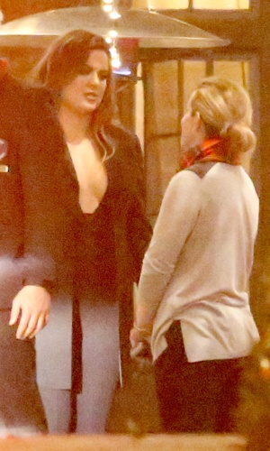 3.dez.2014 - Com superdecote à la Claudia Leitte, Khloé Kardashian é fotografada conversando com uma amiga, após a festa de Natal da empresária Shelli Azoff
