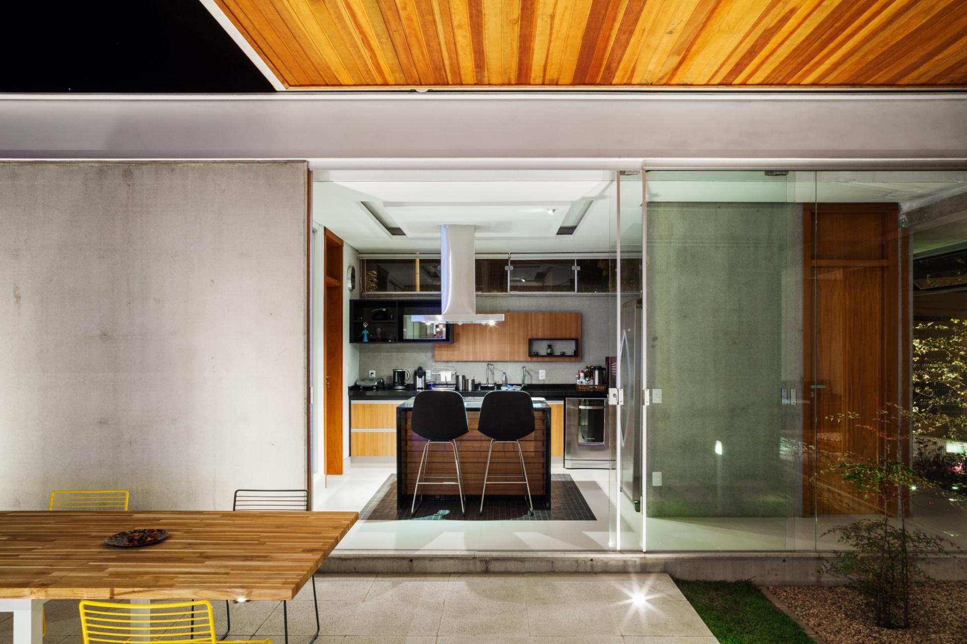 À noite, a cobertura com forro de madeira pode ser fechada e garantir maior proteção à área da churrasqueira interligada à cozinha. A Casa das Pérgolas foi projetada pelo escritório FGMF Arquitetos