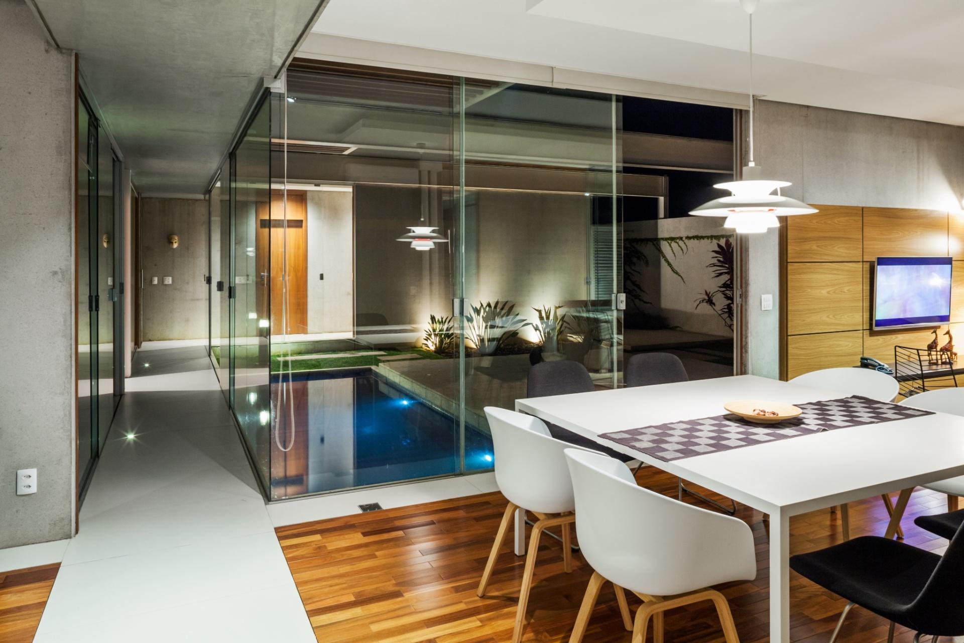 Separados apenas pelos panos de vidro, interior e exterior se fundem na Casa das Pérgolas, projetada pelo escritório FGMF Arquitetos. À direita, está o living, no