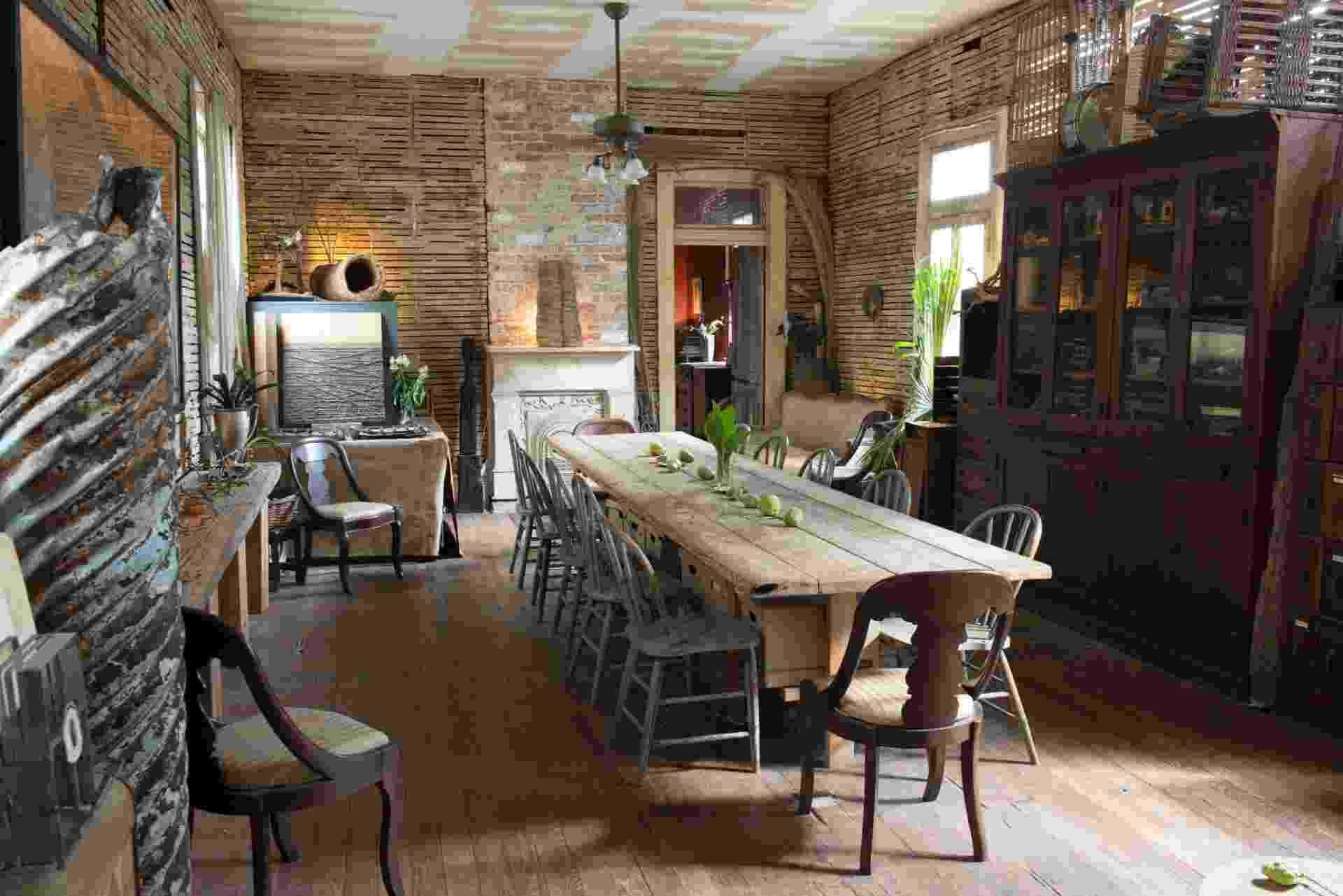 A sala com uma extensa mesa de jantar é o principal cômodo do ateliê de arte de Dawn DeDeaux, que atualmente é usado como casa. O ambiente teve uma parede removida e não é antecedido por um foyer, como de costume nas casas de Nova Orleans (Imagem do NYT, usar apenas no respectivo material) - Paul Costello/ The New York Times