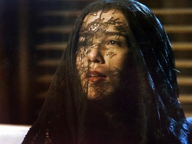 Cora (Marjorie Estiano) usa um véu antes de revelar sua nova aparência ao Comendador em