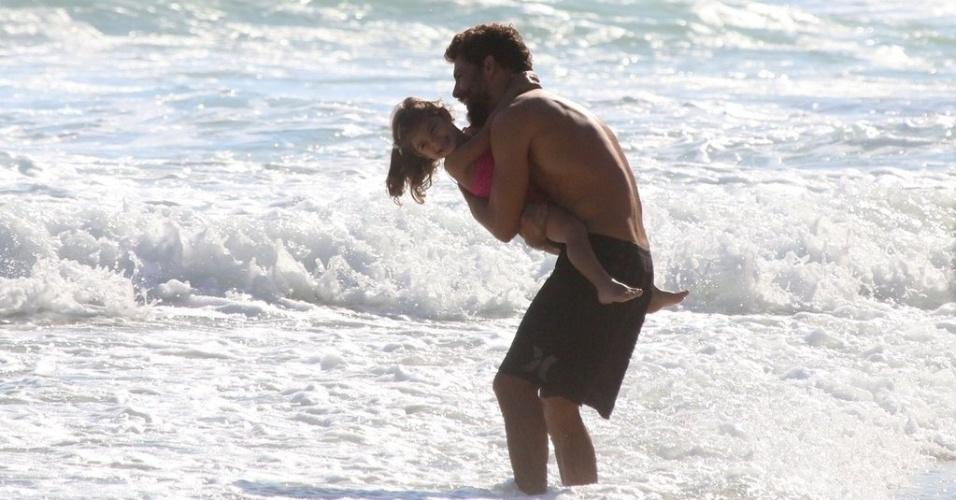 6.dez.2014 - Cauã Reymond brinca com a filha Sofia, de 2 anos, na praia da Joatinga, no Rio de Janeiro. O ator estava no local com a ex-mulher, Grazi Massafera
