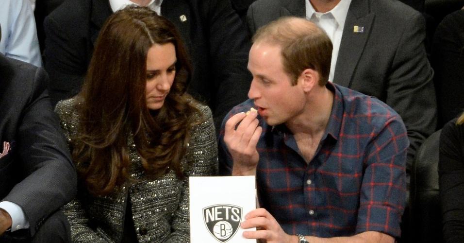 8.dez.2014 - Príncipe William e Kate Middleton assistem a uma partida de basquete da NBA em Nova York nesta segunda-feira. O casal parecia bastante animado durante a disputa entre Brooklyn Nets e Cleveland Cavaliers. Os dois trocaram carinhos durante o jogo