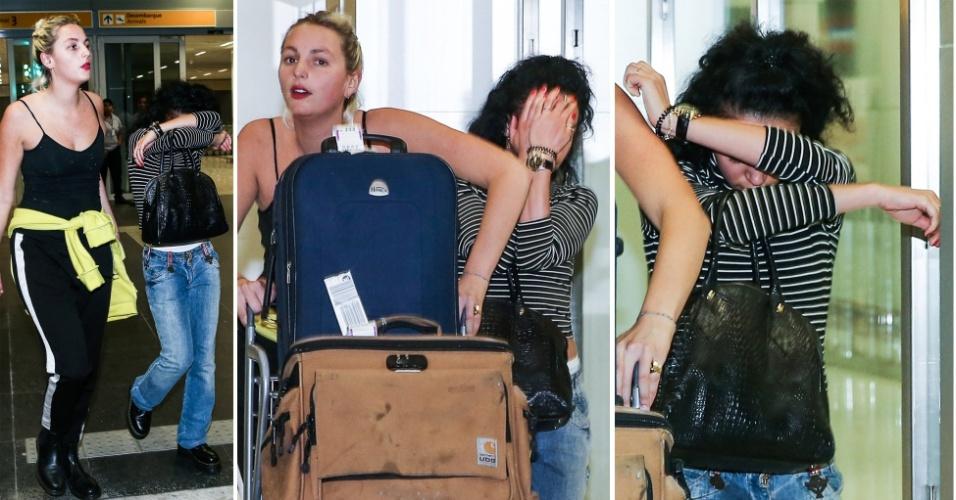 10.dez.2014 - A cantora inglesa FKA Twigs esconde o rosto ao desembarcar no aeroporto de Guarulhos, em São Paulo, na madrugada desta quarta-feira