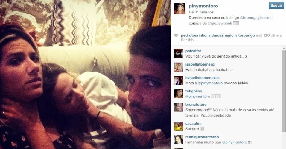 """13.dez.2014 - Giovanna Ewbank aparece sendo enforcada por Bruno Gagliasso ao lado de sua assessora numa alusão ao seu personagem psicopata de """"Dupla Identidade"""", Edu. Piny Montoro, que cuida do casal, foi dormir na casa deles e publicou a imagem após assistirem juntos o penúltimo episódio da série. """"Dormindo na casa do inimigo @brunogagliasso. Coitada da @gio_ewbank"""", escreveu"""