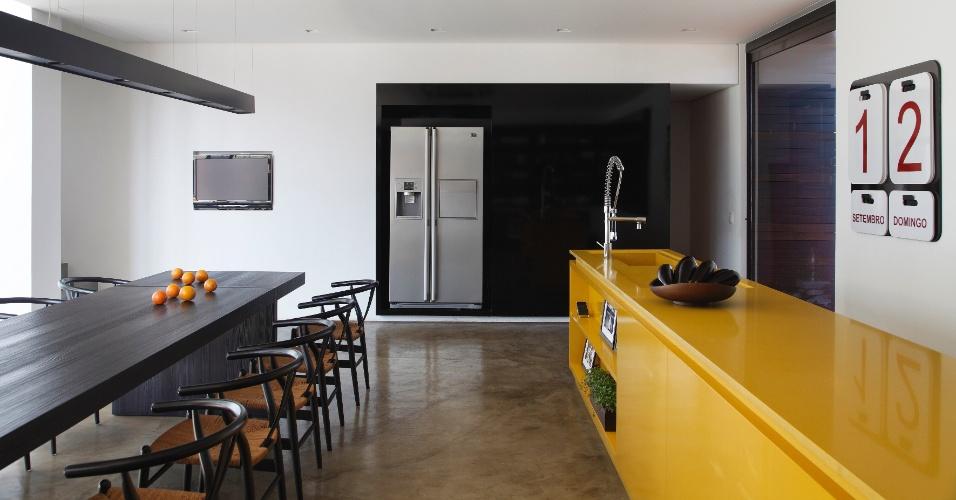 Cozinha e jantar integrados compõem um espaço generoso e harmônico em preto, cinza e amarelo. À esquerda, a mesa de 4,5 m - desenhada por Guilherme Torres (autor do projeto da LA House) - é acompanhada pela luminária de dimensão idêntica, da Wall Lamps