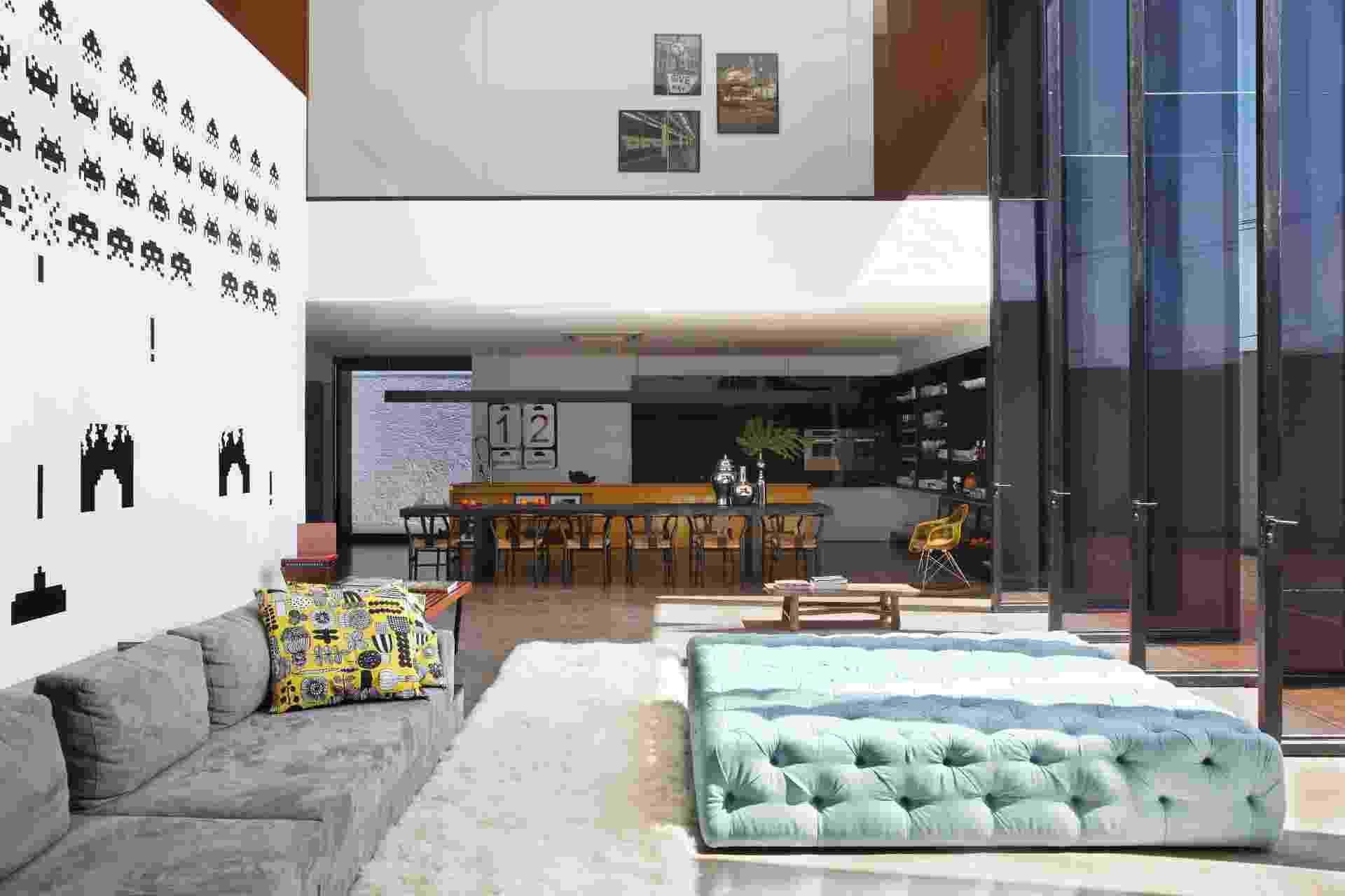 """Além do estar, com sua parede solteira decorada por adesivos dos """"Space Invaders"""", famosos """"personagens"""" do jogo homônimo para o console Atari dos anos 1980, desse ângulo, vê-se a sala de jantar e a cozinha ao fundo e, acima, a parede que delimita os dormitórios. Em primeiro plano, o sofá MiCasa foi combinado ao pufe Miniloft. A LA House foi projetada pelo Studio Guilherme Torres e fica em Londrina (PR) - Denilson Machado (MCA Estúdio)/ Divulgação"""