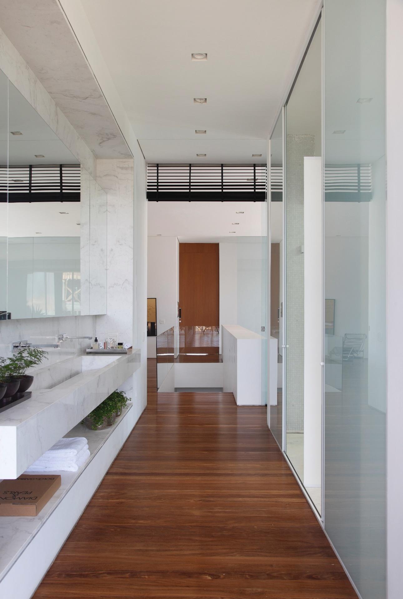 Na suíte do casal, há um corredor entre a bancada da pia (à esq.) e o banheiro (à dir.) separado por portas de correr. O piso é composto por tábuas de cumaru e teto com rebaixo em gesso. A LA House foi projetada pelo Studio Guilherme Torres