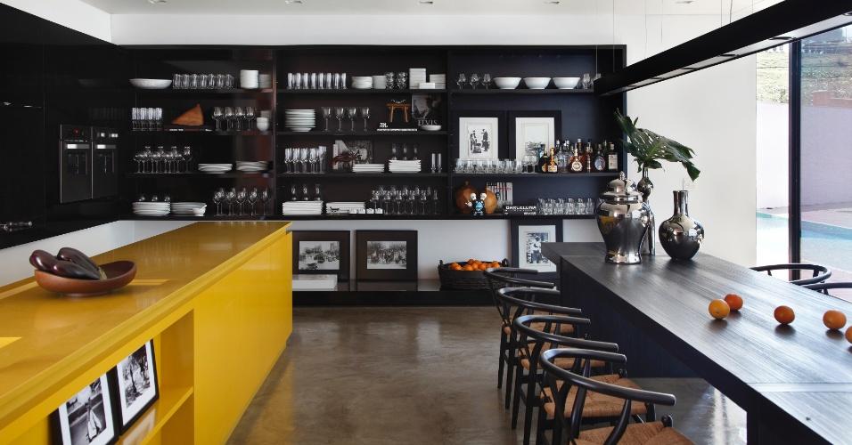 Uma parede inteira foi ocupada pela estante dedicada a guardar louças e cristais. À esquerda é possível observar alguns eletrodomésticos embutidos e, em primeiro plano, a bancada amarela da pia, com nichos para adornos. À direita está a ampla mesa de jantar cercada por cadeiras assinadas por Hans Wegner