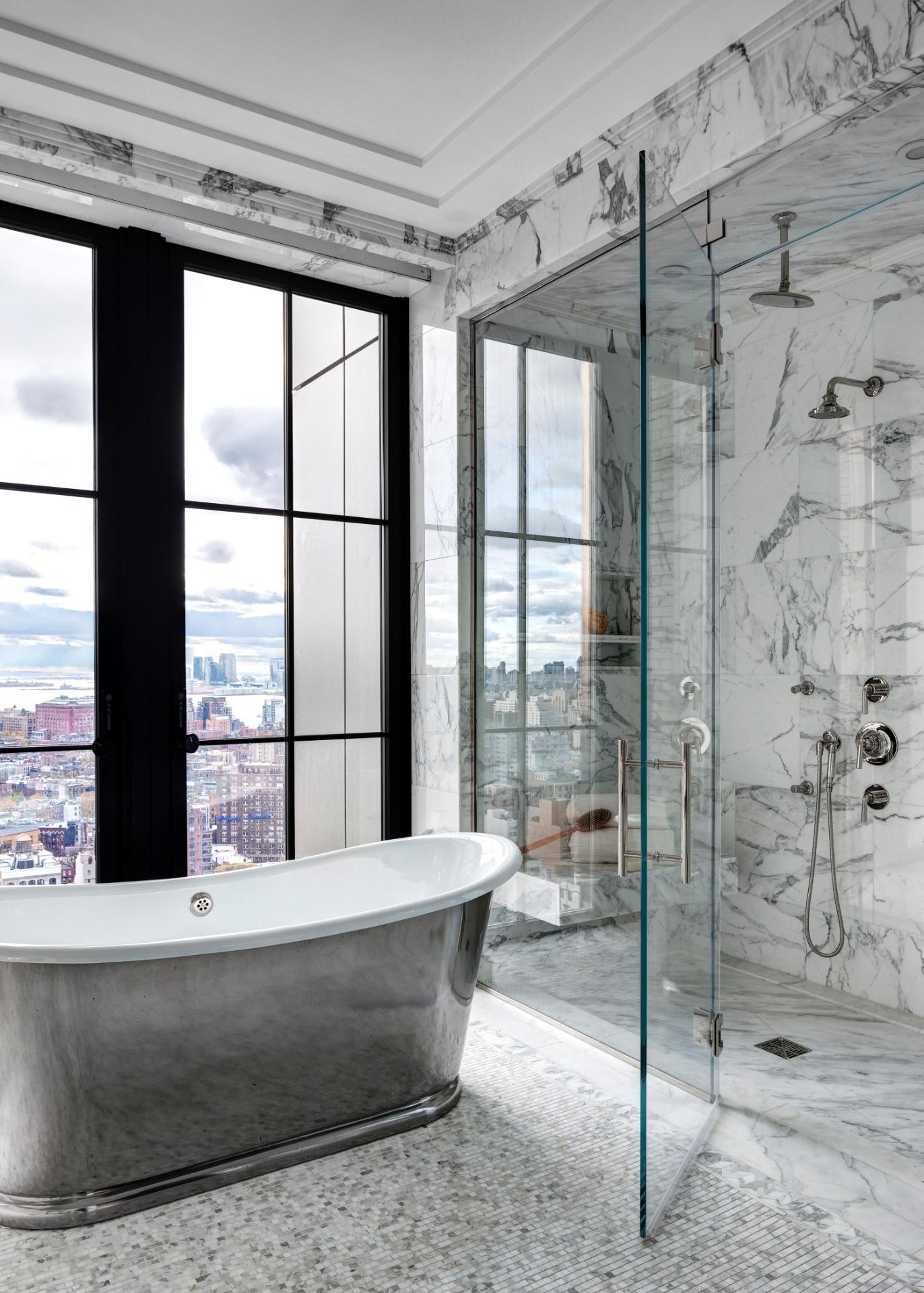 No edifício Walker Tower, localizado na rua 18th West, o banheiro da cobertura é revestido por mármore e tem portas-balcão com envidraçamento generoso. Em frente a uma delas, está posicionada uma elegante banheira com acabamento externo metálico. À direita, no ambiente, uma cabine para banho - Imagem do NYT, usar apenas no respectivo material