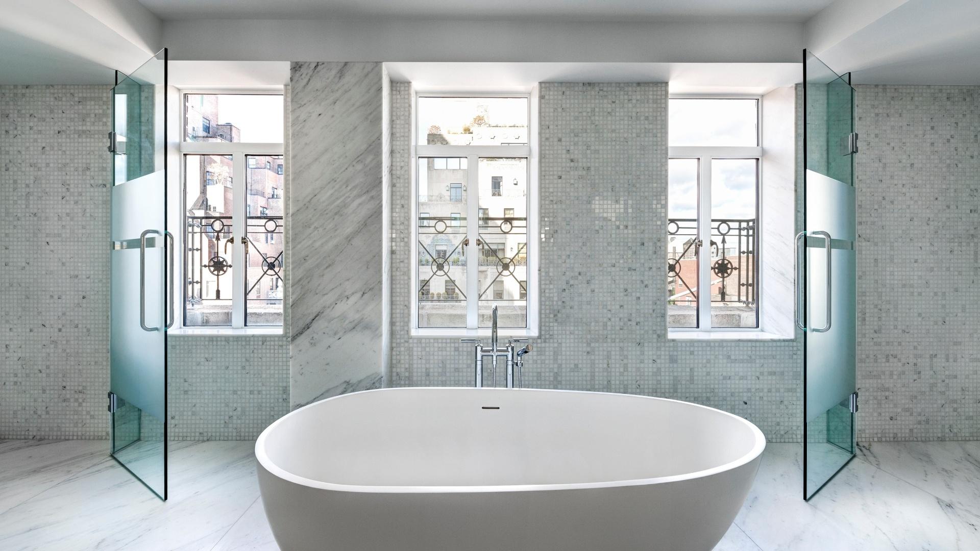 Também na Park Avenue, endereço de luxo de Nova York, o edifício no número 737 possui apartamentos grandiosos. Um dos banheiros das unidades tem revestimento em mármore e janelas grandes, que permitem observar o