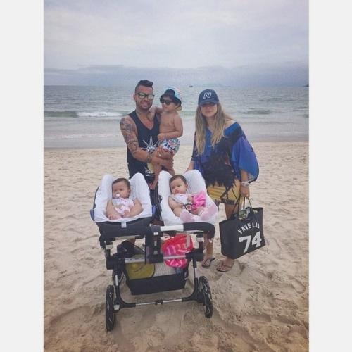 """27.dez.2014 - Dentinho e Danielle Souza levam os filhos à praia. Segundo o jogador, é a primeira vez das gêmeas Rafaella e Sophia, de 8 meses, na beira do mar: """"Primeira vez das nossas princesas na praia!"""", escreveu Dentinho no Instagram"""