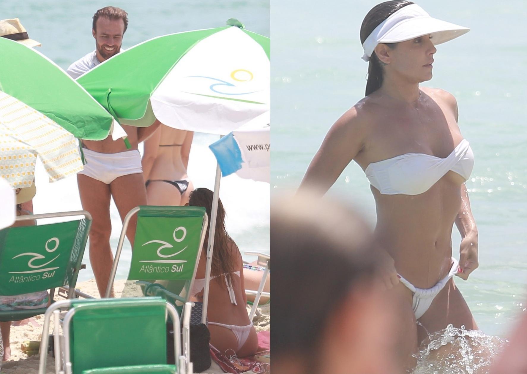 31.dez.2014- De biquíni branco, Deborah Secco se despede de 2014 na praia da Barra da Tijuca, no Rio, e bate papo com o ex-marido Roger Flores