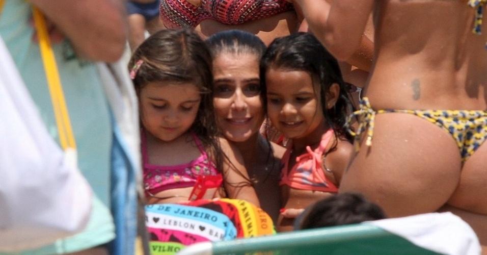 3.jan.2014 - Deborah Secco tira fotos com com crianças na praia da Barra da Tijuca, no Rio