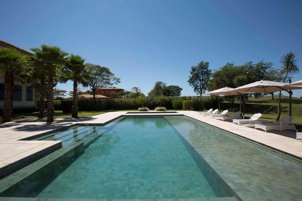 Idealizada para uma casa de campo pelo arquiteto e paisagista Marcelo Faisal, a piscina generosa de alvenaria com spa, banco, degraus e prainha foi revestida por pedra Hijau, coroando a belíssima vista. O piso e a borda são de mármore travertino turco