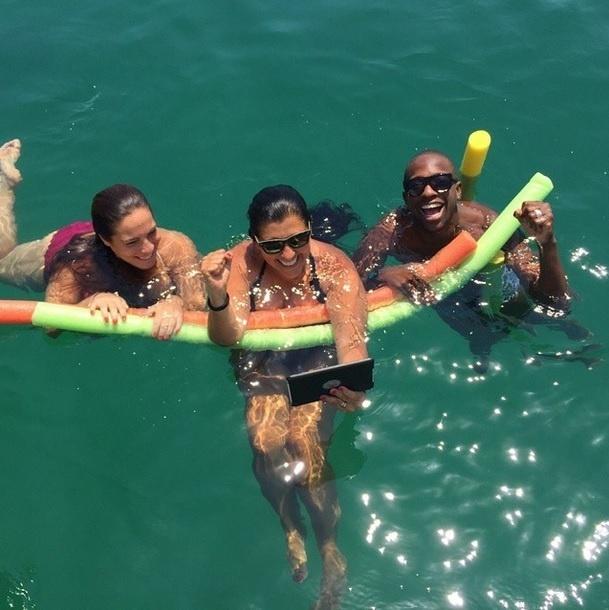 """11.jan.2015 - Em Ilha Grande, no Rio, Regina Casé e Mumuzinho aproveitaram a praia, mas não desgrudaram os olhos da TV enquanto o """"Esquenta"""" deste domingo (11) foi ao ar"""