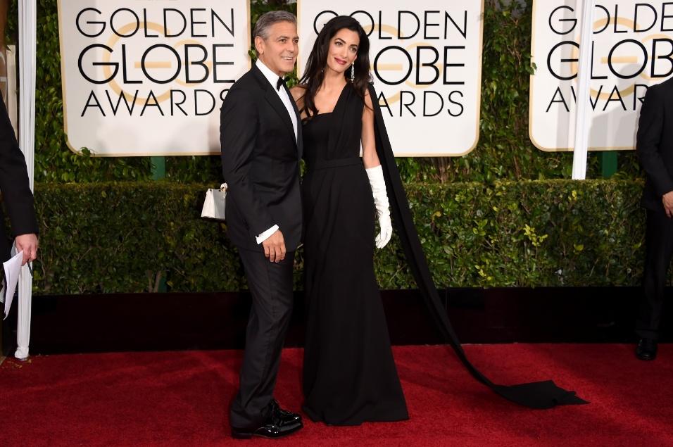 """11.jan.2015 - George Clooney chega à cerimônia do Globo de Ouro com sua esposa, Amal Clooney, que chamou atenção por causa de suas luvas brancas e de um broche usado em sua bolsa, repudiando os atos terroristas registrados na França na última semana. """"É uma homenagem aos franceses, que tiveram uma semana muito difícil"""""""