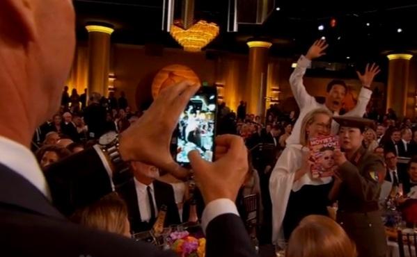 """11.jan.2015 - Acostumado a invadir fotos alheias, o ator Benedict Cumberbatch faz um """"photobomb"""" enquanto Michael Keaton fotografa Meryl Steep e a atriz vestida de jornalista norte-coreana"""