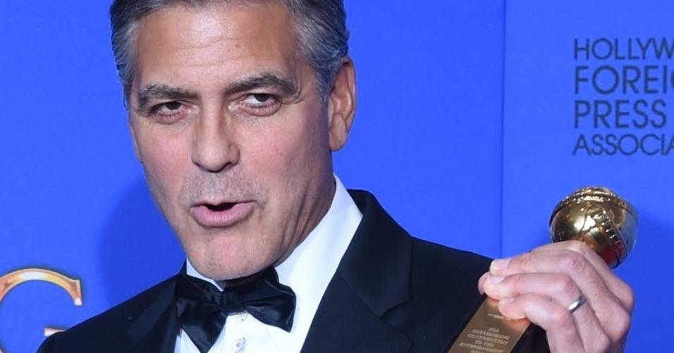11.jan.2015 - George Clooney exibe o prêmio Cecil B. DeMille, que ganhou na cerimônia de gala pelo conjunto de sua obra