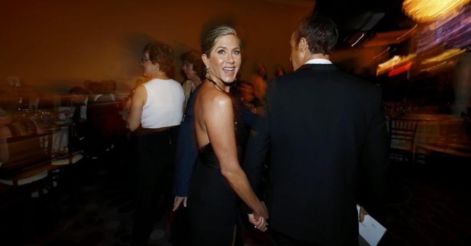 11.jan.2015 - Jennifer Aniston entra no coquetel do Globo de Ouro e segue para sua mesa. Ela foi a primeira celebridade da noite a subir ao palco para apresentar uma categoria