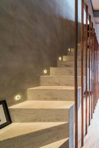 A escada em concreto aparente ganhou fechamento com tubos hidráulicos de cobre (Tigre), fazendo as vezes de guarda-corpo. O material concedeu um ar diferente ao espaço que tem parede com acabamento em tecnocimento, da Bricolagem, e balizadores LED nos degraus, da marca