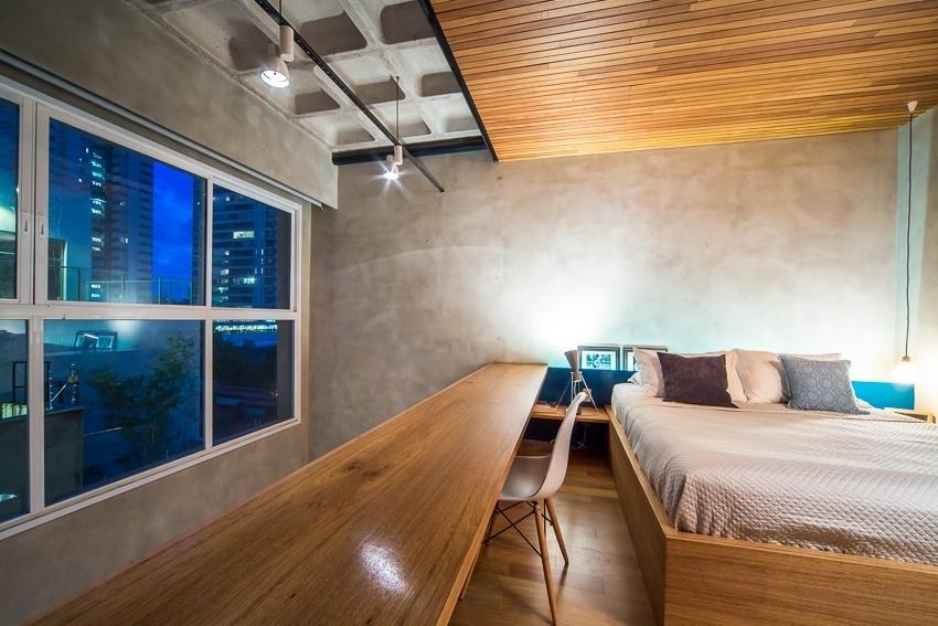 Com a cortina rolô Luxaflex recolhida, pode-se visualizar do mezanino todo o entorno do Apê Cobre Blue, reformado pelo escritório Casa 100 Arquitetura. No dormitório, há harmonia no contraste entre concreto e madeira. Sobre os criados-mudos, as luminárias são da La Lampe