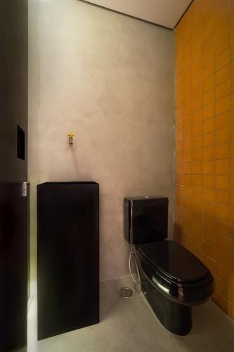 No lavabo, o contraste está nas paredes: uma em ladrilho cerâmico, outra em tecnocimento, assim como o piso. A cuba metálica pintada de preto recebe a companhia da bica de parede Deca. Ao lado, a bacia (também da Deca) com caixa acoplada é preta. O Apê Cobre Blue foi reformado pelo Casa 100 Arquitetura