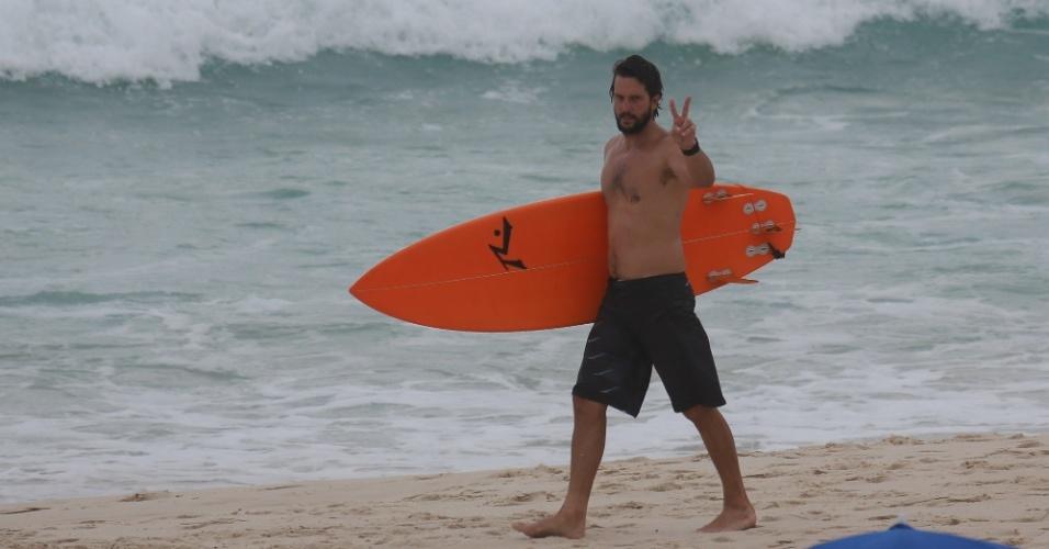 21.jan.2014- Barbudo e quase irreconhecível, Vladimir Brichta acena para fotógrafo após pegar onda na praia da Barra da Tijuca, zona oeste do Rio