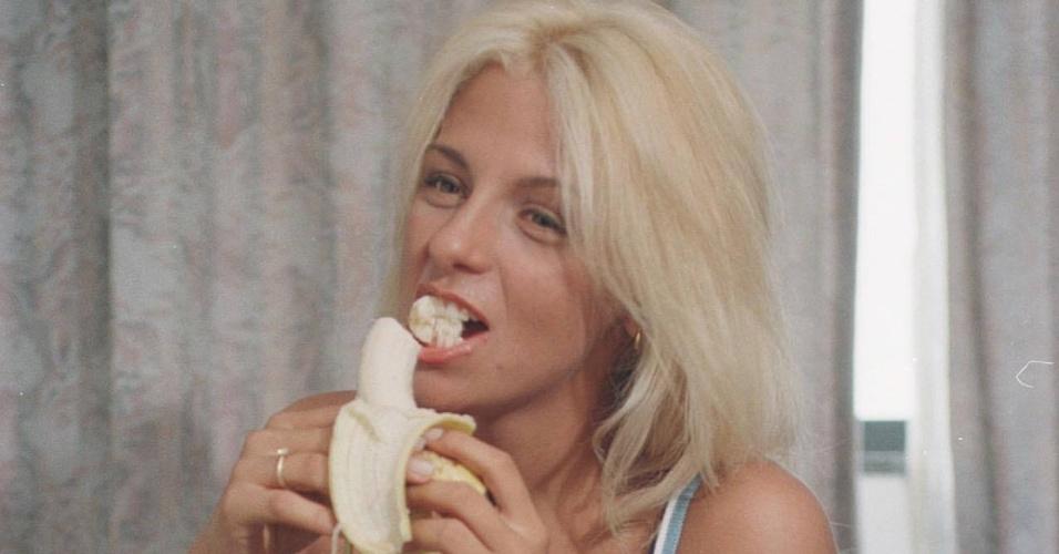 """Carla Perez, ex-dançarina do grupo É o Tchan come banana no hotel Marina Victoria durante o Carnaval de 1998 em Salvador. A Loira iria posar duas vezes para a revista """"Playboy"""" antes de deixar o grupo."""