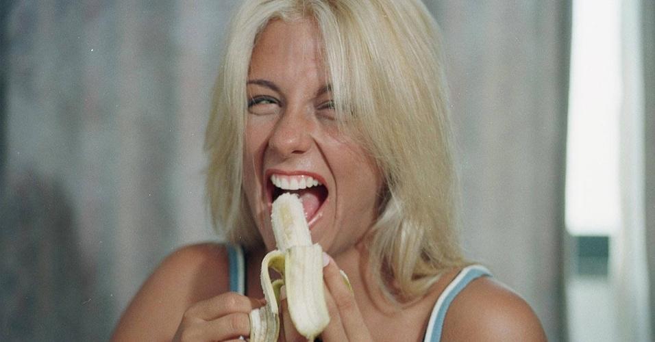 """Ex-dançarina do grupo É o Tchan Carla Perez come banana no hotel Marina Victoria durante o Carnaval de 1998 em Salvador. A loira iria sair do grupo no mesmo ano, sendo substituida por Sheila Mello após concurso no """"Domingão do Faustão""""."""
