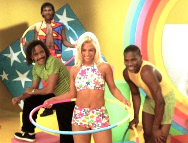 """Integrantes do grupo É o Tchan gravam o comercial divulgando o bambolê """"Bambotchan"""", da Glasslite. Após o lançamento da música """"Bambolê"""", em 1997, o produto foi às lojas."""