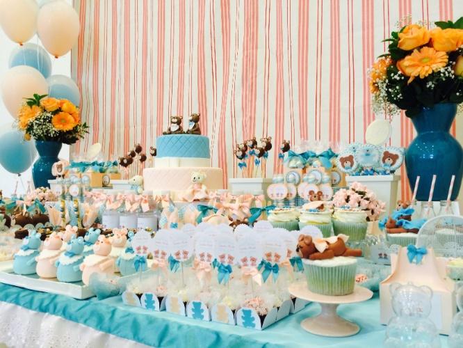 álbum com decorações de chá de bebê de gêmeos   A mesa desse chá de bebê de um casal de gêmeos foi criada em tons de rosa e azul. Optou-se por representar os irmãos em um único bolo, usando as duas cores e dois ursinhos no topo