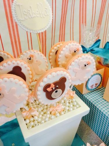 álbum com decorações de chá de bebê de gêmeos   Nesse chá de bebê de um casal de gêmeos, havia um lado da mesa principal dedicado à menina. Nele, os docinhos eram os mesmos do lado do menino, mas feitos em tons de rosa