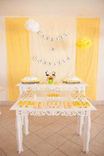 álbum com decorações de chá de bebê de gêmeos | Nesse chá de bebê de um casal de gêmeos, os nomes do irmãos apareceram no painel atrás da mesa principal