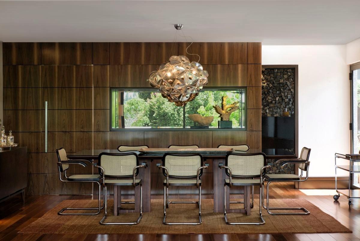 Sóbria, a sala de jantar foi montada a partir da mesa fornecida pela Simmetria associado a exemplares da clássica cadeira Cesca, desenhada por Marcel Breuer. Buscando uma linguagem um pouco mais minimalista e que evidencia a nobreza dos materiais, a parede que separa o ambiente da cozinha foi revestida com chapas de nogueira americana, executadas pela D'Arte Móveis. A casa em Curitiba (PR), teve arquitetura e design de interiores projetados por Jorge Elmor