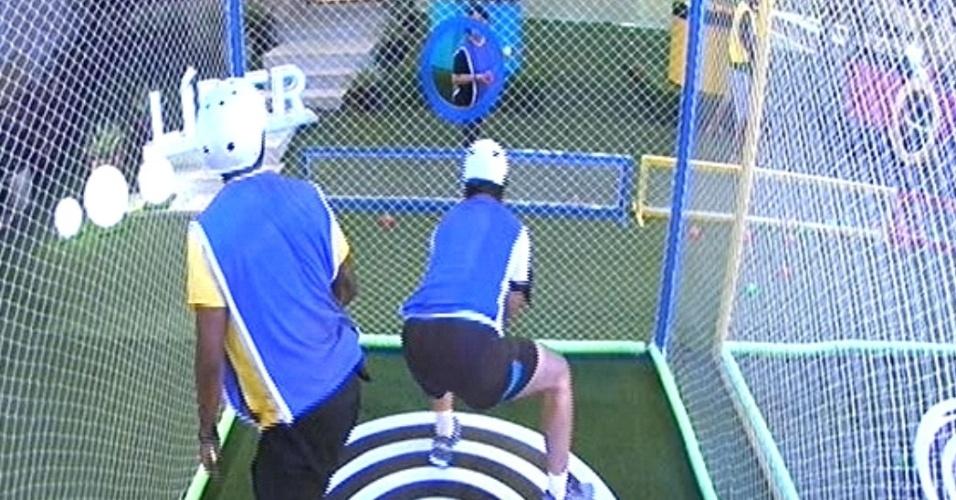 """29.jan.2015 - Douglas e Marco, integrantes do grupo azul, se revezam dentro da gaiola para apanhar bolinhas jogadas por Mariza na primeira prova do líder do """"BBB15"""""""